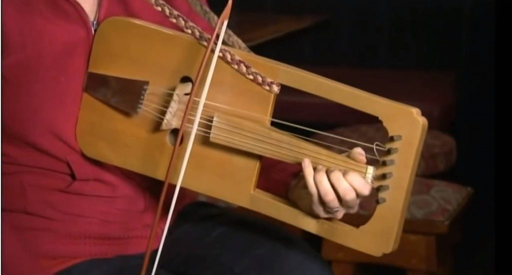 Cass Meurig playing the crwth and demonstrating it to Paul Martin. The solo tune we hear her play is the traditional Welsh Black-Haired Crwth Players Tune. Click on the picture to start the video, which opens in a new window.